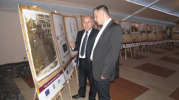 K. Kozicki i ks. Robert Czeladko podziwiają wystawę fotografii dotyczących świątyni w Piątnicy.