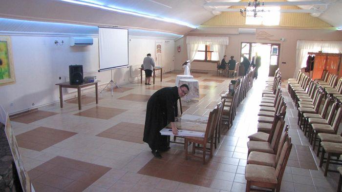 Ks. Paweł Grala w trakcie wykonywania czynności porządkowych po konferencji.