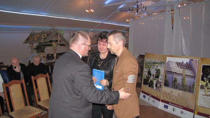 Ks. proboszcz Dobecki wręcza album rodzicom śp. Konrada Steca, który wykonał zdjęcia wnętrza kościoła i jego elementów wyposażenia.