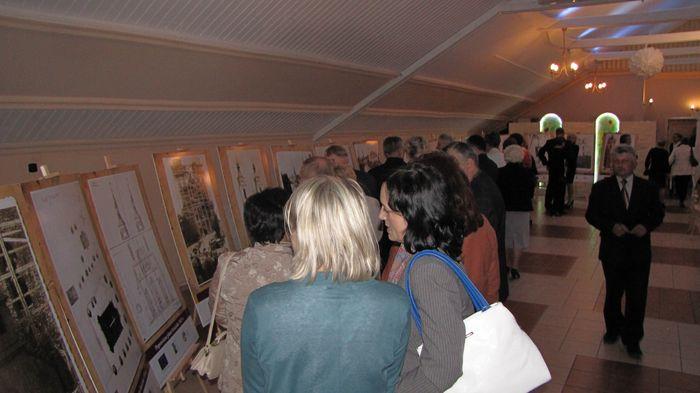 Uczestnicy konferencji podziwiaja wystawę fotografii dotyczących kościoła w Piątnicy.