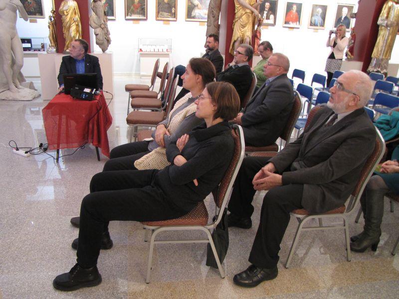 Przy czerwonym stoliku prowadzący wykład Pan Czesław Rybicki i zaproszeni goście