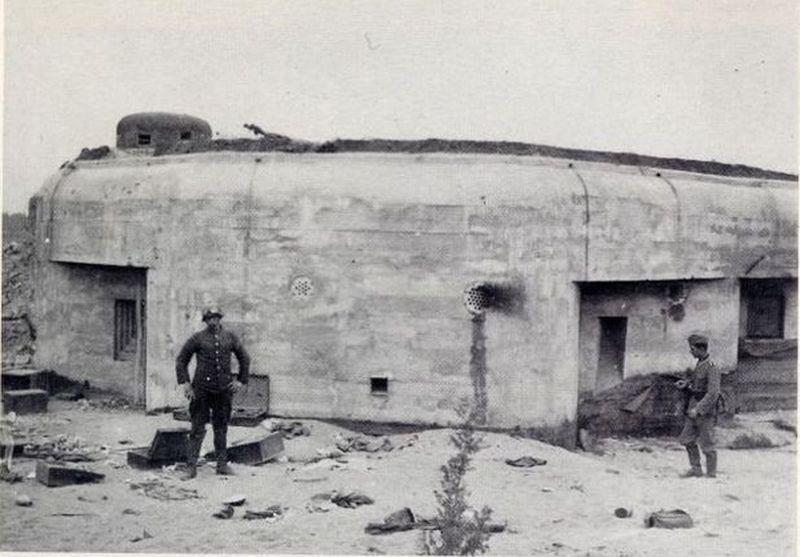 Tylna ściana schronu. Widoczne od lewej: strzelnica obrony bezpośredniej, obok odstrzelona krata przeciwszturmowa, zrzutnia granatów, druga strzelnica obrony bezpośredniej i wyjście zapasowe