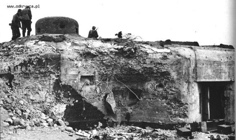 Zniszczona lewa strzelnica w ścianie schronu i widoczna, zasłaniająca strzelnicę broni ręcznej, bryła betonu