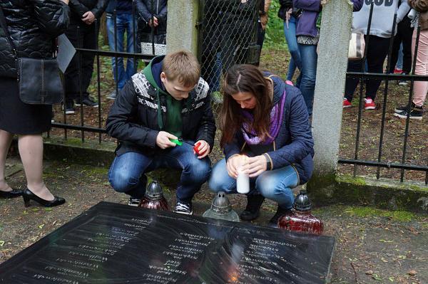 Michał Kisiel z koleżanką zapala znicz na grobie zakładników miasta Łomży