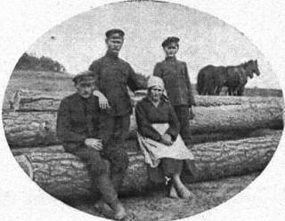 Grupa osadników w Grzybowie pod Słonlmem; dwaj stojący z Małopolski, para siedząca z miejscowej szlachty zagrodowej poleskiej. Cieszą się nadzieją bliskiej budowy—drzewo już zwiezione.