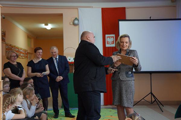 Sekretarz Łomżyńskiego Bractwa Historycznego wręcza nagrodę pani minister Annie Marii Anders