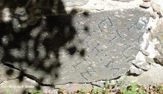Kamień w ogrodzeniu kościoła z elementem innej inskrypcji