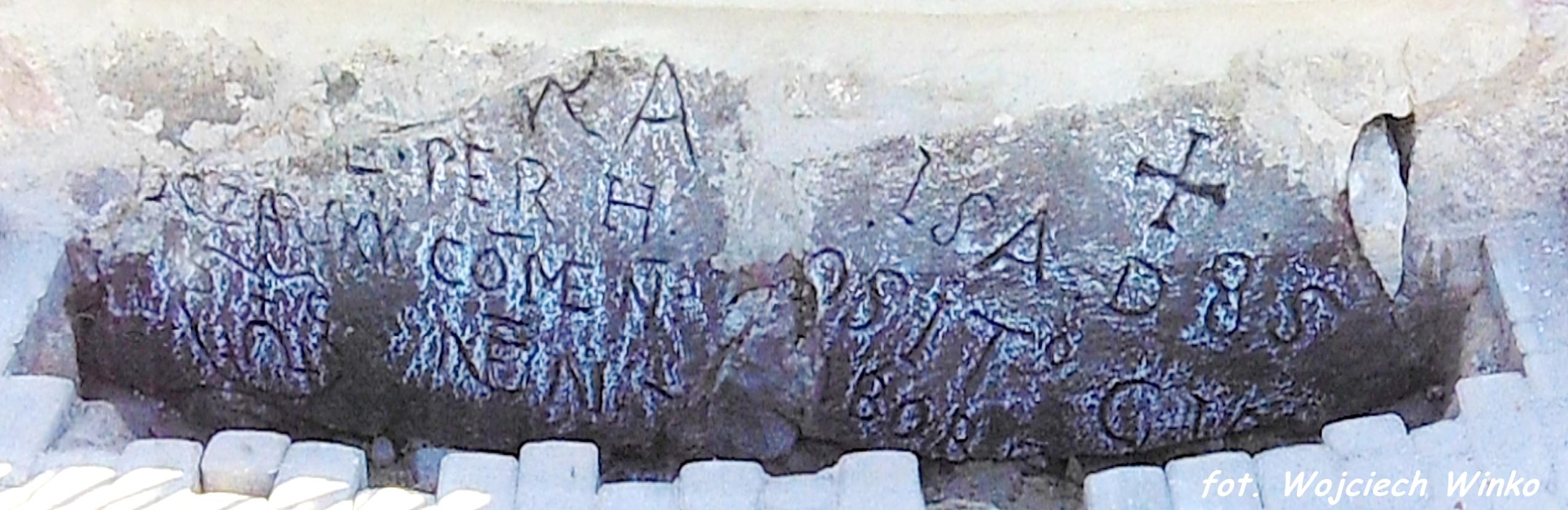 Kamienne bloki z wyrytą inskrypcją w fundamencie ogrodzenia