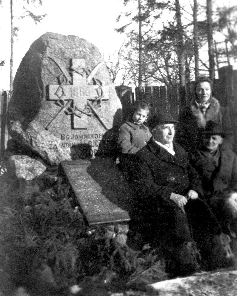 Grupa turystów przy pomniku.